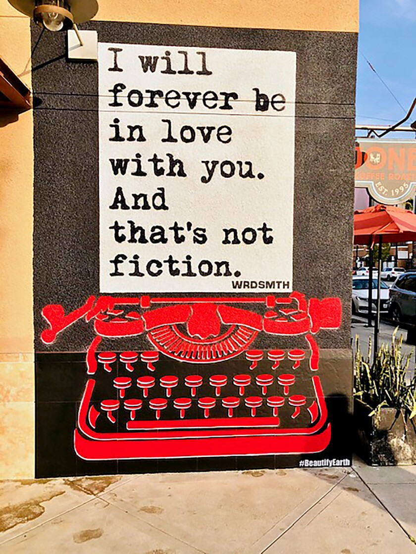 "A mural of a red typewriter and piece of paper with the words ""I will forever be in love with you. And that's not fiction."""