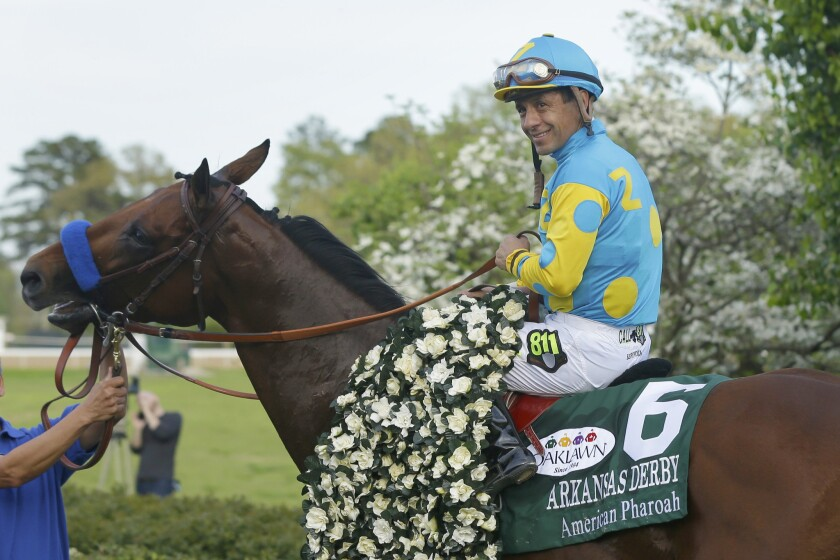Jockey Victor Espinoza poses with American Pharoah after winning the 2015 Arkansas Derby.
