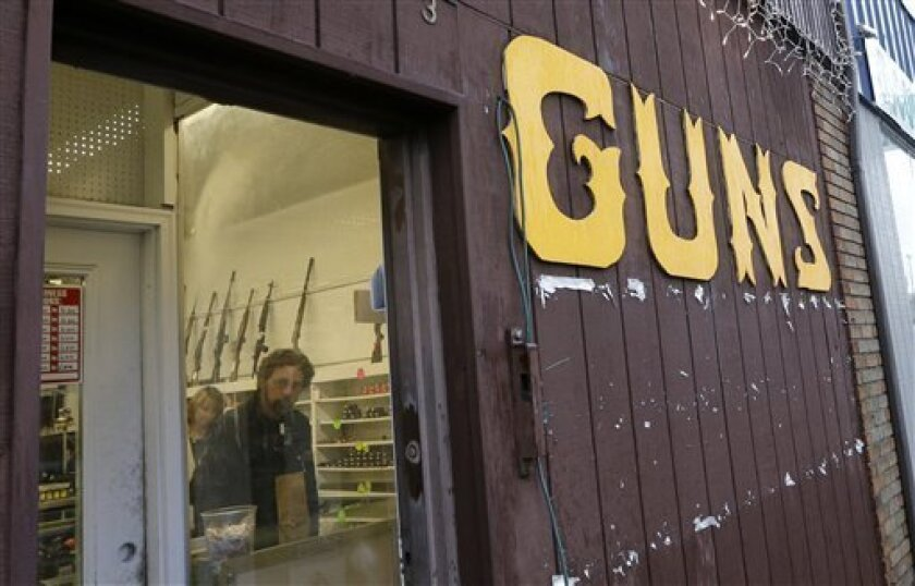 Rifles line a wall above in front of people standing in a gun shop Wednesday, Dec. 19, 2012, in Seattle. (AP Photo/Elaine Thompson)