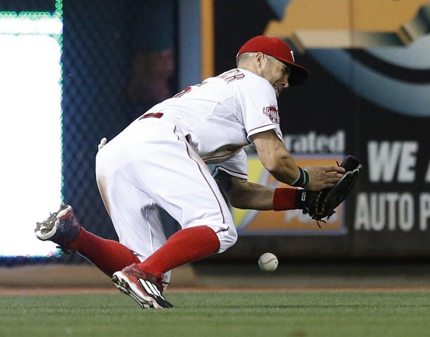 Cincinnati Reds left fielder Skip Schumaker can't retrieve the ball hit by Arizona Diamondbacks A.J. Pollock during the seventh inning of a baseball game, Thursday, Aug. 20, 2015, in Cincinnati. (AP Photo/Gary Landers)