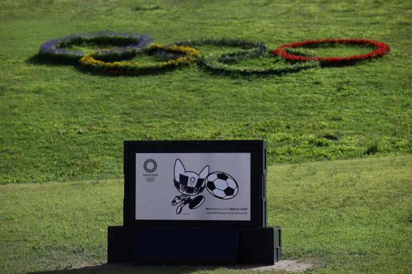 La mascota olímpica en blanco y negro patea un balón de fútbol en una pancarta en los Juegos Olímpicos de Tokio.