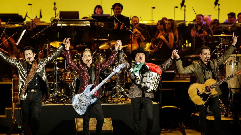 Members of Los Tigres del Norte take a bow before the Youth Orchestra Los Angeles at the Hollywood Bowl.