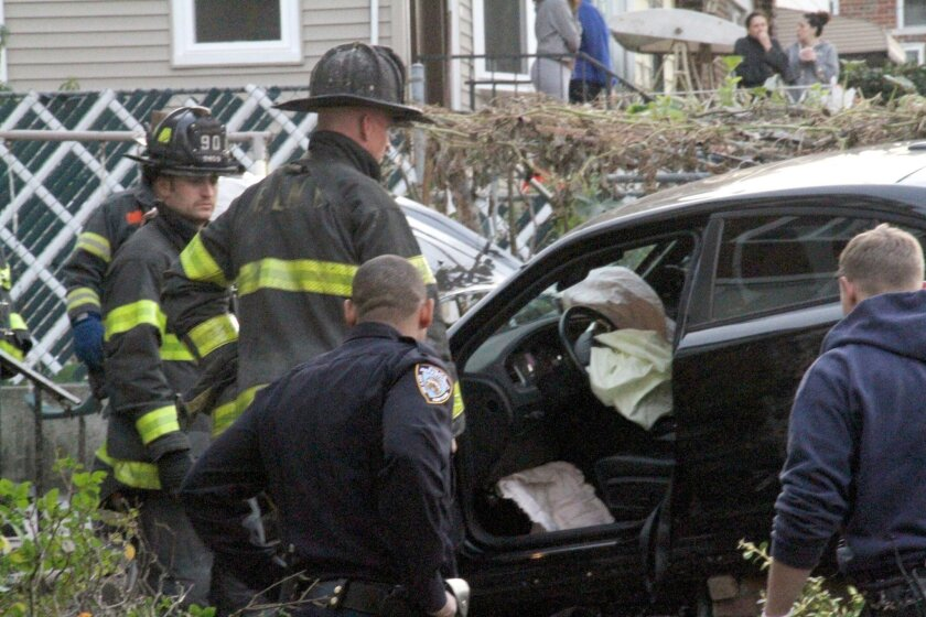 First responders examine an automobile after its driver lost control and plowed into a group of trick-or-treaters in New York, Saturday, Oct. 31, 2015. Three people were killed, including a 10-year-old girl. Several others were injured. (AP Photo/David Greene)