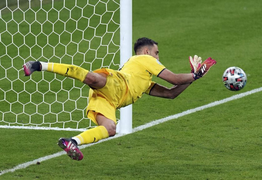 Italy goalkeeper Gianluigi Donnarumma makes a saves on a penalty shot from England's Bukayo Saka during the penalty shootout during the Euro 2020 soccer championship final match between England and Italy at Wembley Stadium in London, Sunday, July 11, 2021. (Mike Egerton/PA via AP)