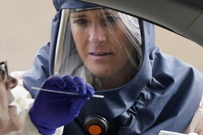 Salt Lake County Health Department public health nurse Lee Cherie Booth performs a coronavirus test Friday in Salt Lake City.
