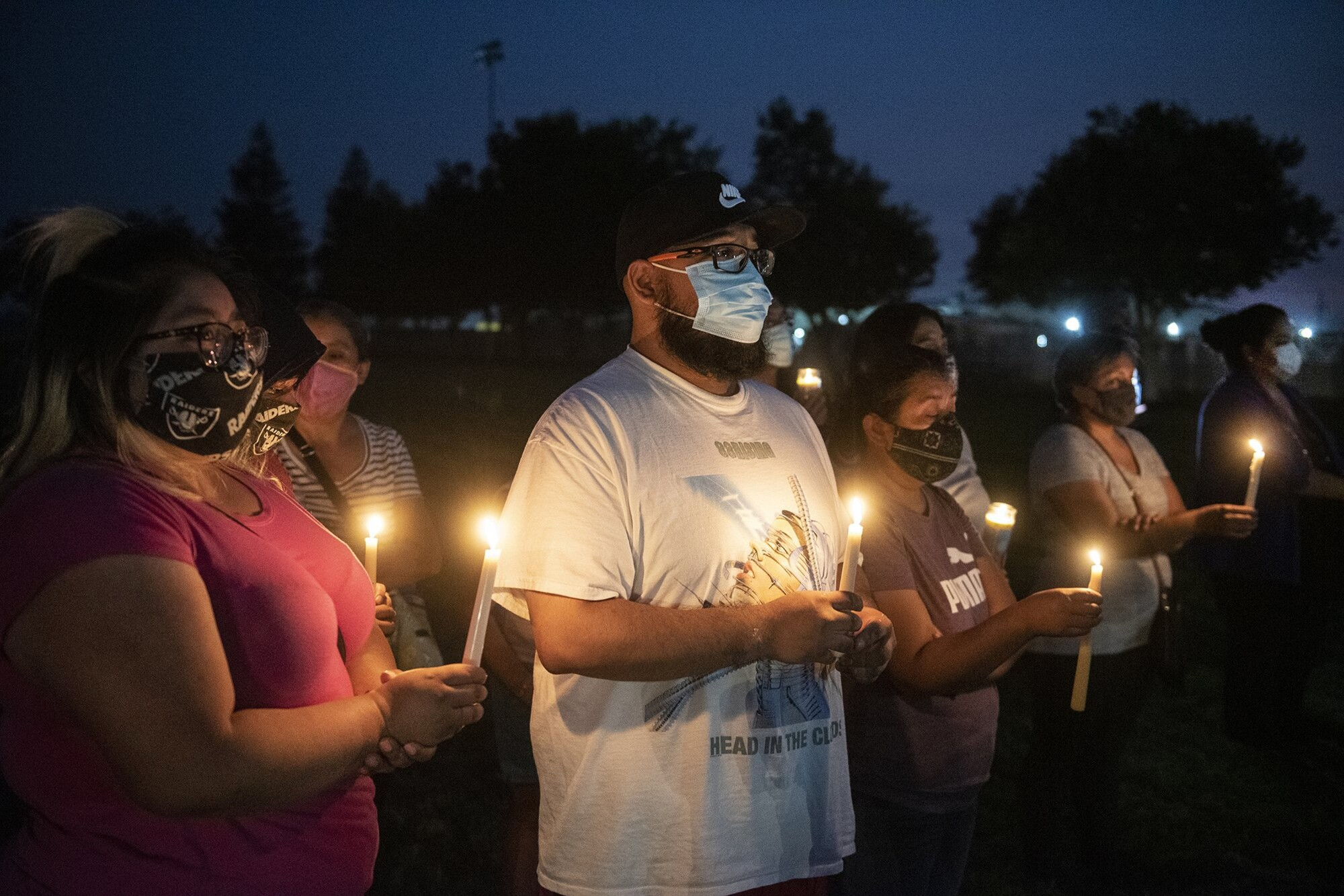 Foster Farms employee Kevin Vera, 28, of Livingston, center, attends a community candlelight vigil in Livingston, Calif.