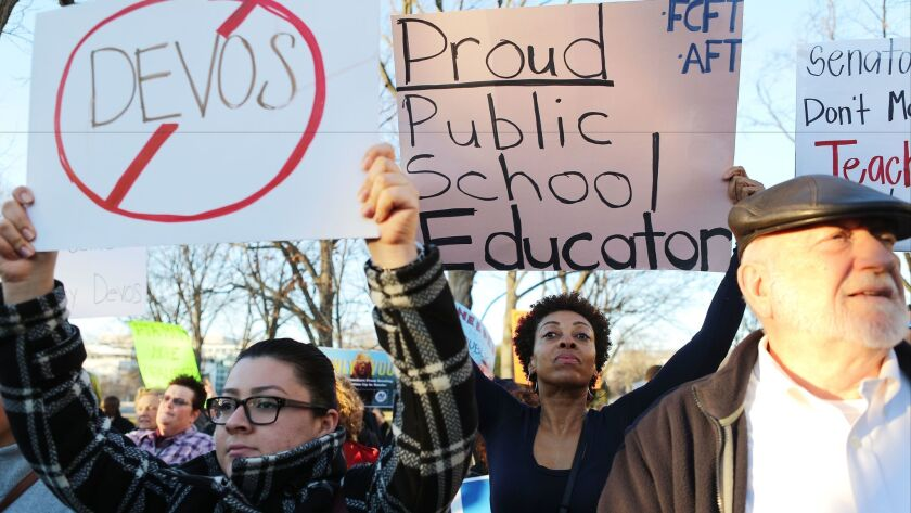 Protesters demonstrate against Betsy DeVos in Washington on Monday.