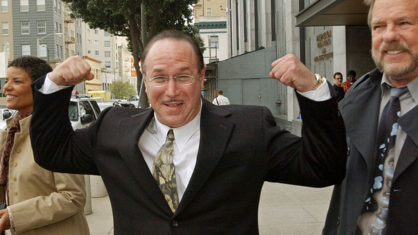 Victor Conte, nutritional adviser and founder of the Bay Area Laboratory Co-Operative (BALCO), flexes his muscles as he leaves a federal courthouse in San Francisco on March 26, 2004.