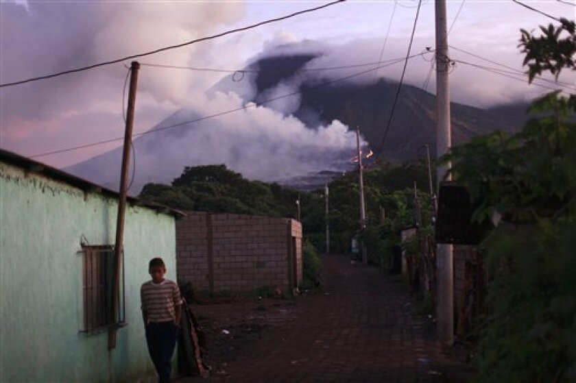 A villager walks backdropped by the erupting Pacaya volcano in Villa Canales, 50 kms south of Guatemala City, Saturday, June 5, 2010. The volcano started erupting lava and rocks last May 27, forcing thousands of people to flee their homes and disrupting air traffic as ash drifted over major cities.