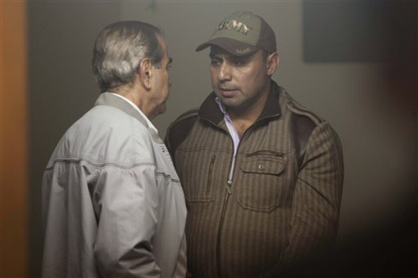 Former Guatemalan army captain Byron Lima Oliva, accused and sentences to jail for the slaying of Archbishop Juan Gerardi in 1998,  right, talks with a unidentified man while waiting in a courtroom in Guatemala City, Friday, Feb. 15, 2012. Lima who was supposed to be in jail serving a 20 year sente