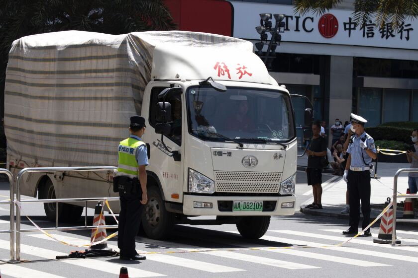 """A movers' truck with the words """"Liberation"""" on top arrives outside the United States Consulate in Chengdu, China"""