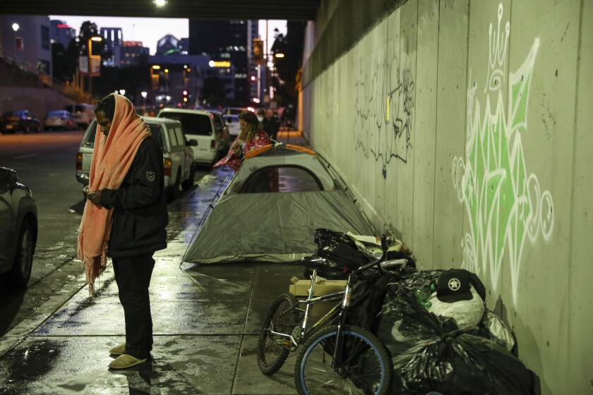 A homeless couple sets up a tent under the City College bridge.
