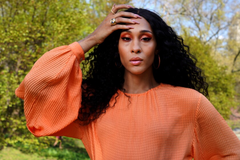 'Pose' actor Mj Rodriguez in an orange top with her hand on her head, pictured outdoors
