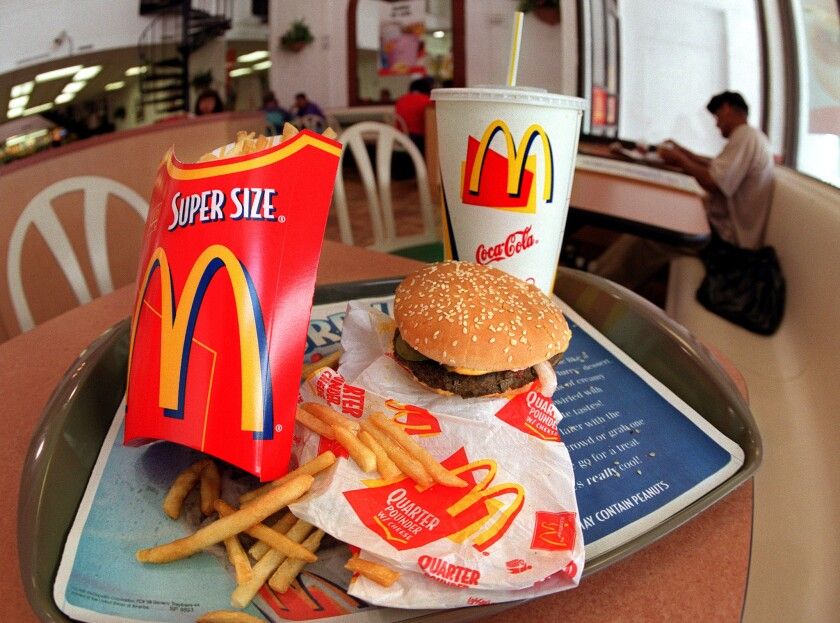 A Quarter Pounder with cheese, fries and a soda at a McDonald's restaurant.