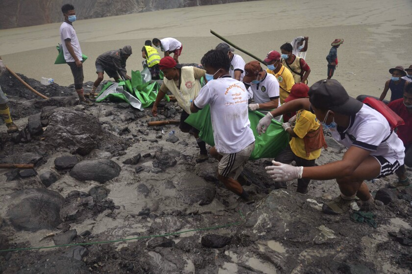 People pull a green plastic that shrouds a recovered body Friday, July 3, 2020 in Hpakant, Kachin State, Myanmar. Over 100 people were killed Thursday in a landslide at a jade mine in northern Myanmar, the worst in a series of deadly accidents at such sites in recent years.(AP Photo/Zaw Moe Htet)