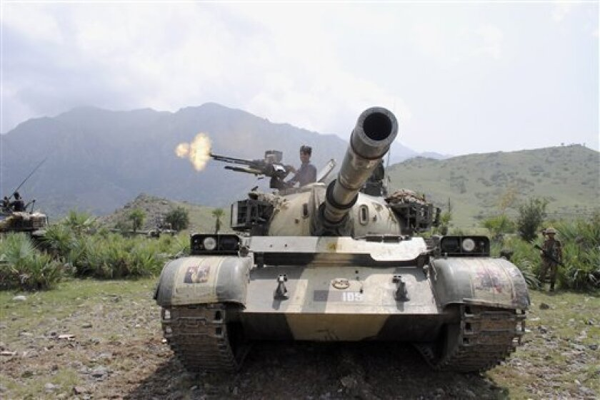 A Pakistani army soldier fires toward a target at a forward base during a military operation against militants in Pakistan's Khurram tribal region, Sunday, July 10, 2011. A military operation in Kurram tribal region has been launched to clear the area of terrorists involved in various terrorist activities, including kidnapping and killing of locals, suicide attacks and blocking the road connecting lower with upper Kurram, Pakistani army spokesman Maj. Gen. Athar Abbas said. (AP Photo/Mohammad Zubair)