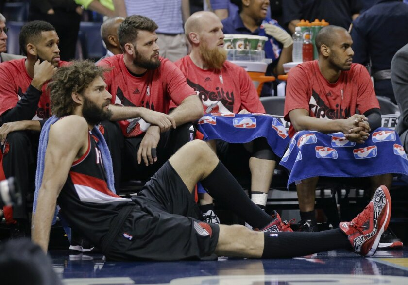 Portland Trail Blazers center Robin Lopez sits on the floor as players watch the final minutes of the second half of Game 5 of an NBA basketball Western Conference playoff series against the Memphis Grizzlies Wednesday, April 29, 2015, in Memphis, Tenn. The Grizzlies won 99-93 to win the series 4-1