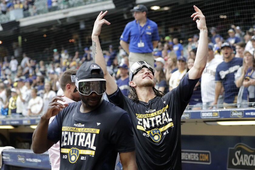 Milwaukee Brewers' Josh Hader, right, gestures to fans as he walks back onto the field after a baseball game against the New York Mets, Sunday, Sept. 26, 2021, in Milwaukee. The Brewers clinched the National League Central Division. (AP Photo/Aaron Gash)
