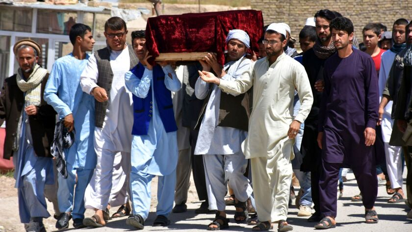 Men carry the coffin of one of the victims of Friday's attack at a military compound in Mazar-i-Sharif province north of Kabul, Afghanistan, on April 22, 2017.