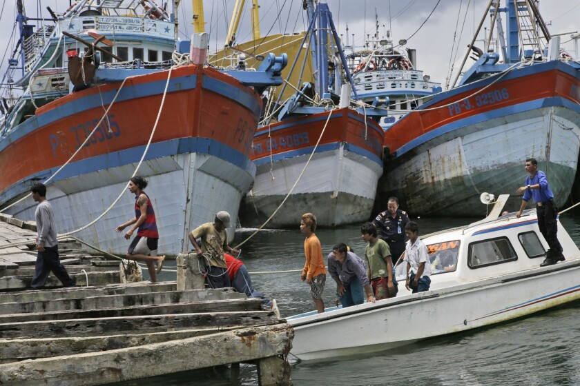 Burmese fishermen arrive at the compound of Pusaka Benjina Resources in Benjina, Aru Islands, Indonesia as hundreds of foreign fishermen rush at the chance to be rescued from the isolated island where slavery runs rampant in the industry.
