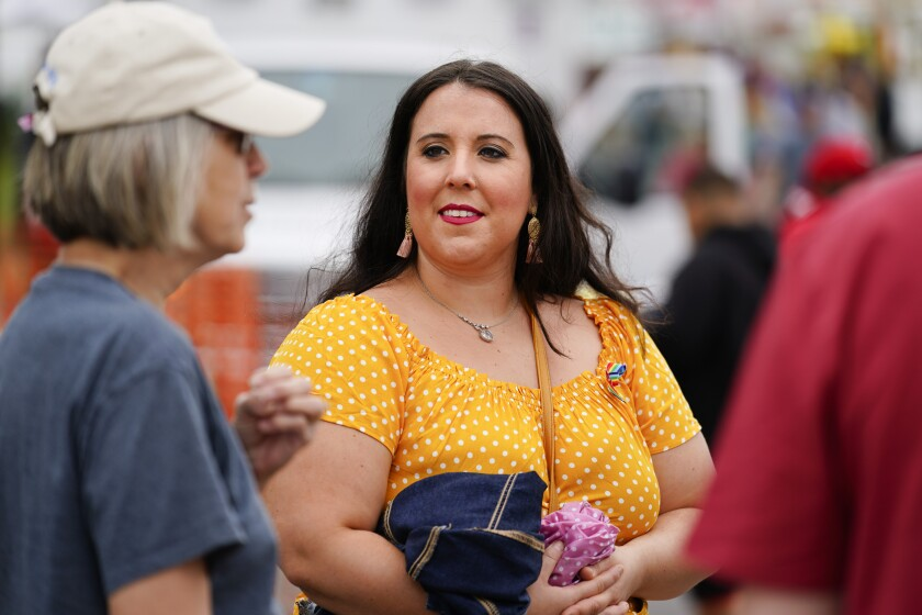 Alicia Duque, a 35-year-old mother of three and volunteer organizer for the progressive group, Action Together listens to Claudia Glennan at the Edwardsville Pierogi Festival in Edwardsville, Pa., Friday, June 11, 2021. (AP Photo/Matt Rourke)
