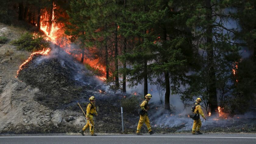 Firefighters monitor flames above California 299 while battling the Carr fire west of Redding on Monday.