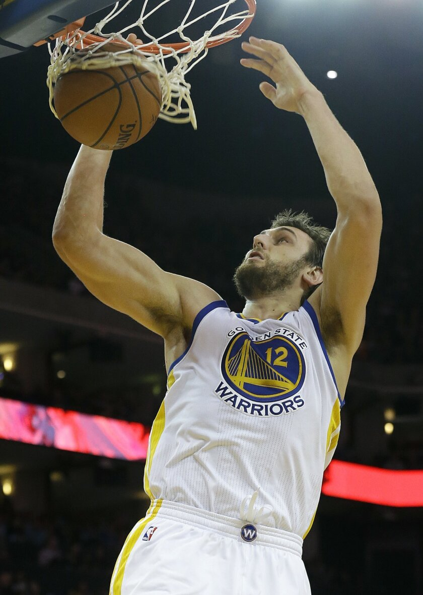 FILE - In this March 16, 2015, file photo, Golden State Warriors center Andrew Bogut (12) dunks against the Los Angeles Lakers during the second half of an NBA basketball game in Oakland, Calif. The Warriors bet on Bogut when they signed him to a long-term extension before last season. And Bogut bet on himself with the way the deal was structured. Both sides are reaping the rewards. (AP Photo/Jeff Chiu, File)