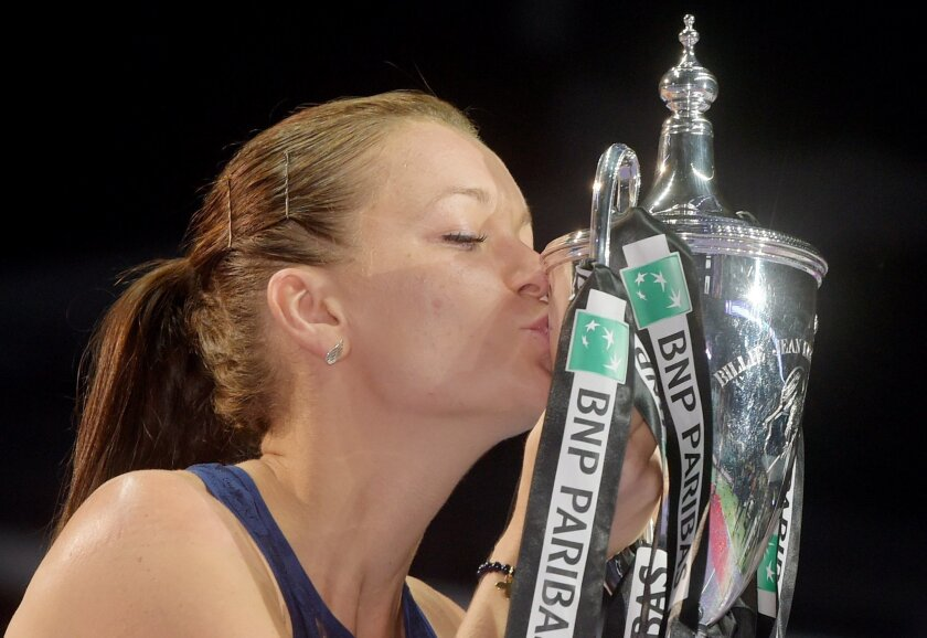Agnieszka Radwanska of Poland kisses the trophy for photographers after she won the singles final against Petra Kvitova of the Czech Republic at the WTA tennis finals in Singapore on Sunday, Nov. 1, 2015.  (AP Photo/Joseph Nair)