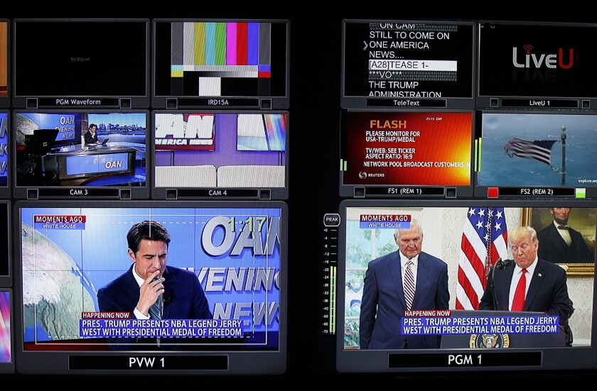 Screens show different segments for a nightly news segment in the control room at One America News