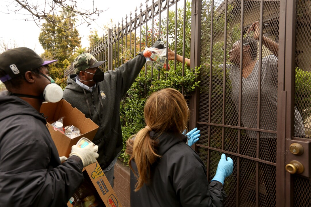 """Ansar """"Stan"""" Muhammad, center, executive director of H.E.L.P.E.R. Foundation, delivers food through a fence to the needy in the Oaklwood Neighborhood of Venice on April 9, 2020. Members with H.E.L.P.E.R. Foundation deliver food and groceries to the needy, those who have lost their jobs and seniors who are sheltering in place in the neighborhood due to the COVID-19 pandemic."""