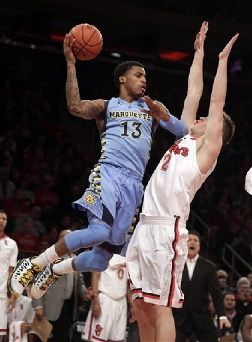 Marquette's Vander Blue, left, goes up against St. John's Marc-Antoine Bourgault during the first half of an NCAA college basketball game at New York's Madison Square Garden, Saturday, March 9, 2013. (AP Photo/Richard Drew)