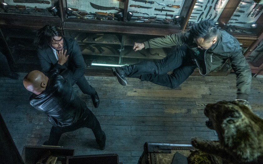 "A scene from ""John Wick 3"" with Keanu Reeves fighting amid a knife exhibit."