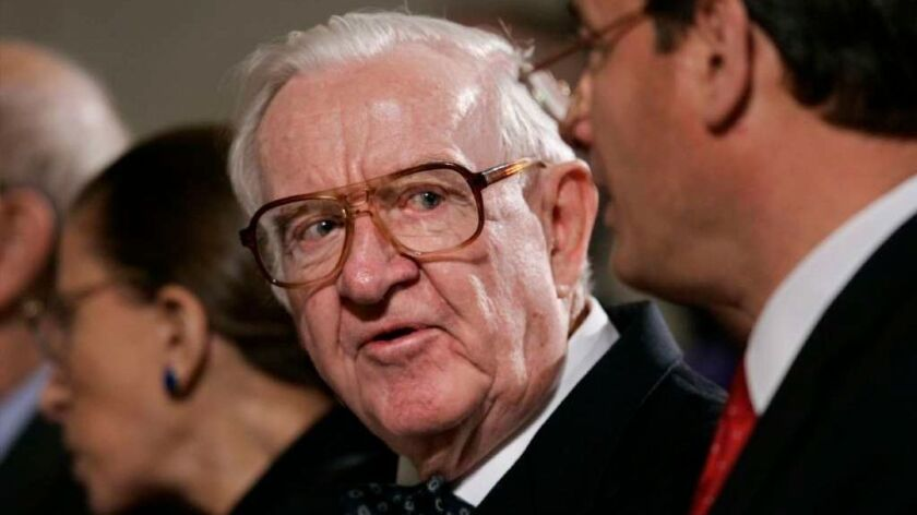 In this 2006 photo, Associate Justice John Paul Stevens talks with Chief Justice John G. Roberts, right, just before the start of a memorial for the late Chief Justice William H. Rehnquist at the Supreme Court in Washington.