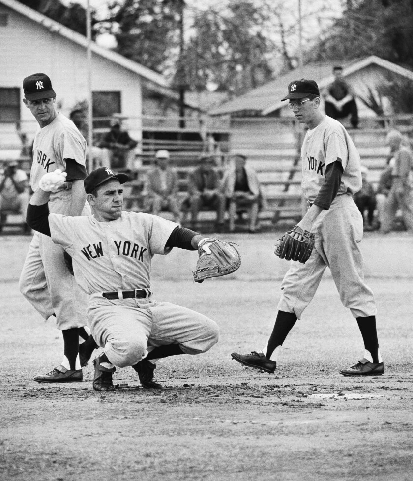 FILE - In this February 1958 file photo, New York Yankee catcher Yogi Berra, troubled with a skin infection, wears white gloves to protect his hands as he warms up a pitcher during baseball spring training in St. Petersburg, Fla. Walking behind Yogi are outfielder John Reed and infielder Phil Linz, right. Linz, who knocked a Game 7 home run off Bob Gibson in the 1964 World Series but made even more noise by hitting a few sour notes on his harmonica, has died. He was 81. Former teammates said Linz's family told them he died Wednesday night, Dec. 9, in Leesburg, Va. Linz had been in poor health since a stroke five years ago. (AP Photo/Harry Harris, File)