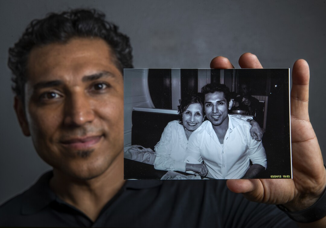 Disney character designer José  Zelaya holds a photograph taken in 2012 of him and his mother, Degni Garcia Menendez.