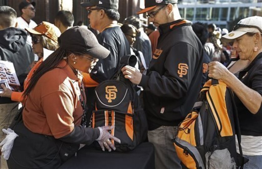 In this photo taken Tuesday, April 23, 2013, fans have their backpacks searched by security personnel prior to entering AT&T Park for a baseball game between the Arizona Diamondbacks and the San Francisco Giants in San Francisco. Major League Baseball's previously scheduled security meeting in New