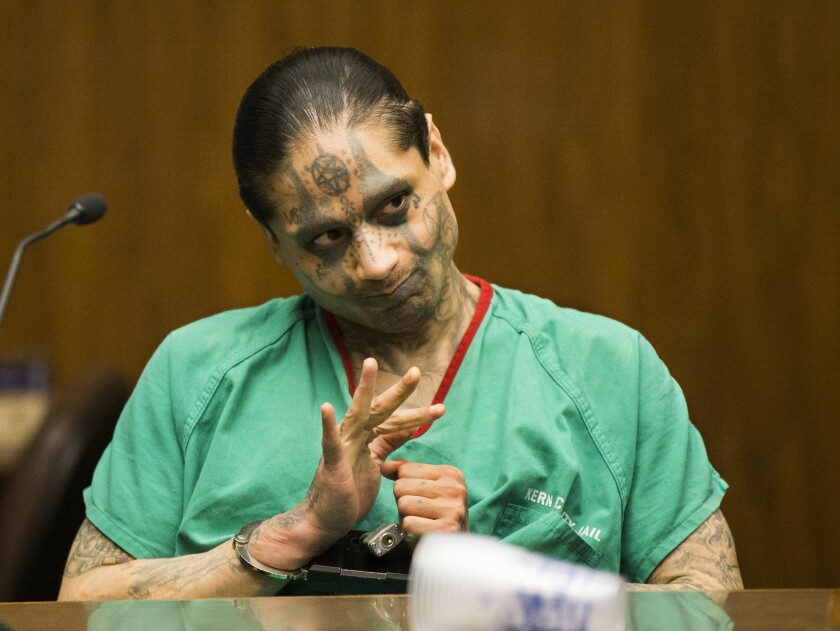 A man with tattoos all over his face and body and his hands in handcuffs sits at a table.