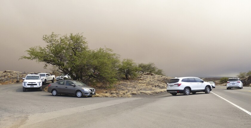 Vehicles turn onto Queen Kaahumanu Highway from an emergency access route opened after residents and visitors lodging in the Waikoloa Village area of Hawaii were ordered to evacuate as a wildfire threatened the South Kohala town Sunday, Aug. 1, 2021. (Chelsea Jensen/West Hawaii Today via AP)