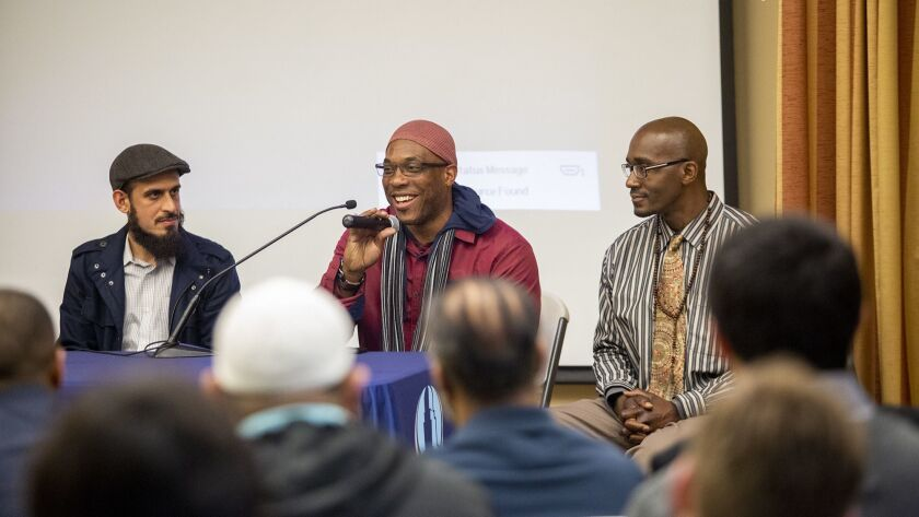 Amin Eshaiker, left, the program manager for Link Oustide, listens as Tobias Tubbs, 48, speaks about life in prison, during an Islamic Institute of Orange County meeting on Feb. 15. Also in the photo is Gernay Quinnie Jr., 37.