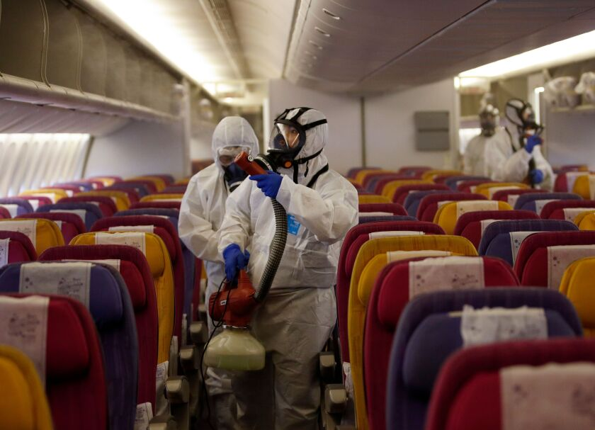Technicians spray disinfectant on an airplane in Thailand