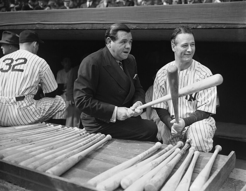 "These two famous baseball players are shown in the Yankee dugout before the beginning of the Second World Series Game between the Yankees and Cincinnate Reds on Oct 5, 1939 in New York. Babe Ruth, the old swatsmen, fondles a bat in a seemingly ""Rarin' to go"" way while first baseman Lou Gehrig, out"