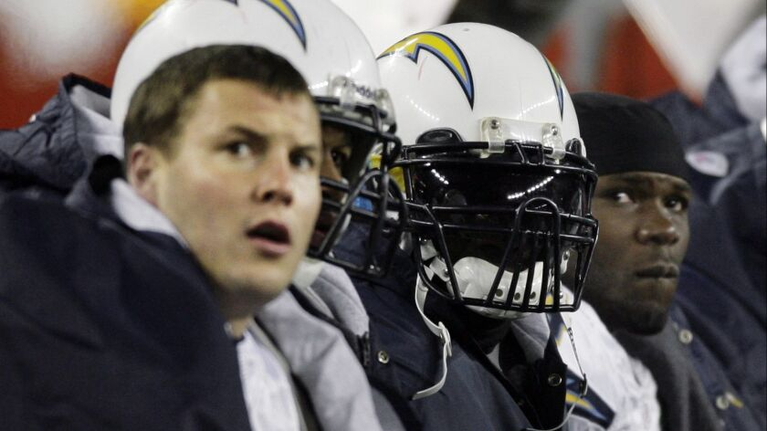 Chargers quarterback Philip Rivers, left, running back LaDainian Tomlinson, second from right, and fullback Andrew Pinnock sit on the bench during the third quarter of the AFC Championship football game against the New England Patriots on Jan. 20, 2008.