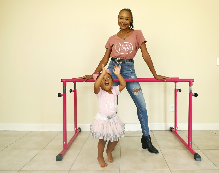 Lisa McCabe stands at a ballet barre, smiling. Her 2-year-old daughter dances in front of her in a tutu.