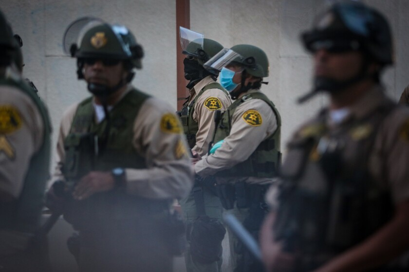 Deputies stand guard during a protest outside the sheriff's station in Compton on June 21.