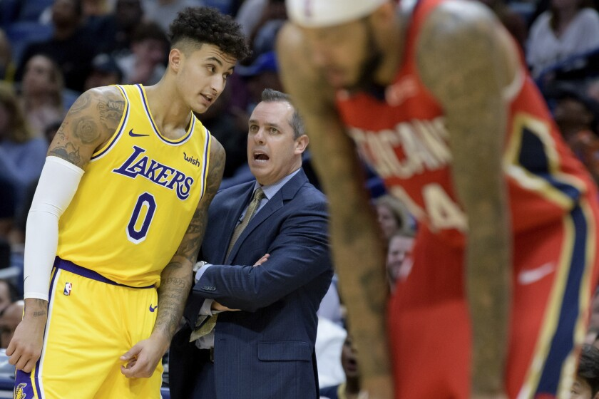 Lakers coach Frank Vogel talks to forward Kyle Kuzma (0) during a break in play Wednesday night in New Orleans.