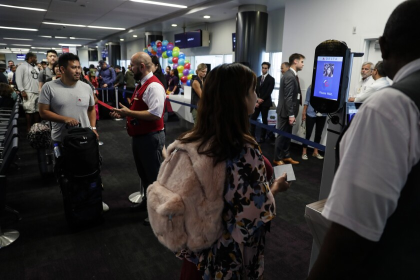 Airline passengers wait to go through an airport security checkpoint.