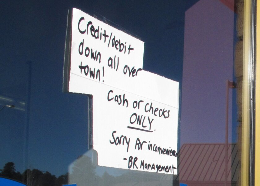 A sign posted outside a Baskin-Robbins ice cream store in Flagstaff, Ariz., Wednesday advises customers that only cash or checks will be accepted due to an Internet and phone outage.