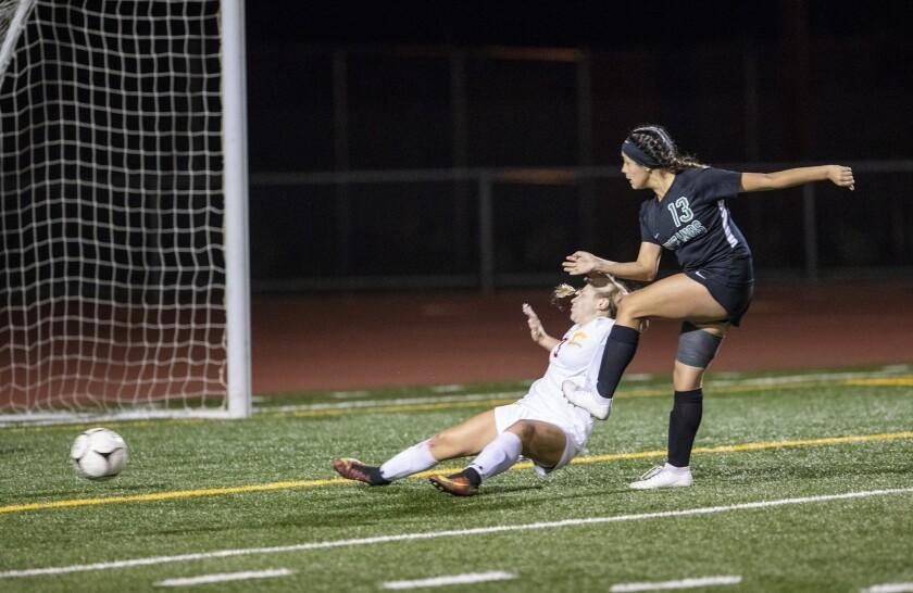 Costa Mesa's Natalia Guzman scores a goal on Hillcrest's defender Kaila Smith during the quarterfina