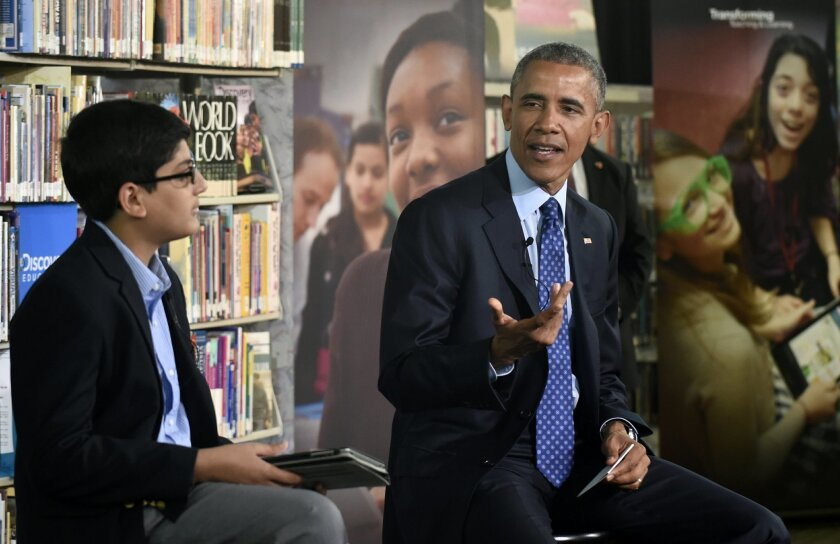 "President Barack Obama, sitting next to 6th-grader Osman Yaya, a student at Wicomico County Public Schools' Bennett Middle School in Salisbury, Md., speaks at Anacostia Library in Washington, Thursday, April 30, 2015, as he participates in a live ""virtual field trip"" with middle school students to"