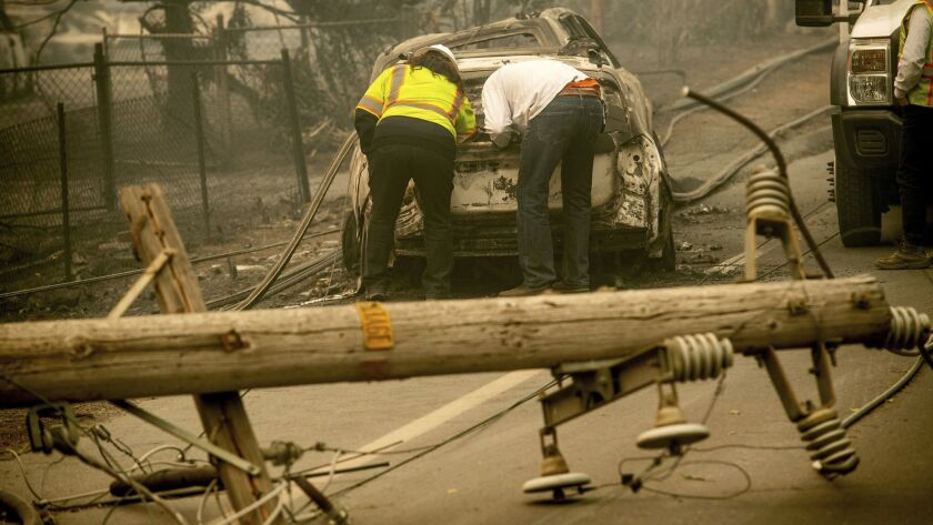 Two men look through a vehicle with a downed utility pole in the foreground after the Camp fire burned through Paradise, Calif., in November. PG&E is facing billions in potential damages because of the disaster.